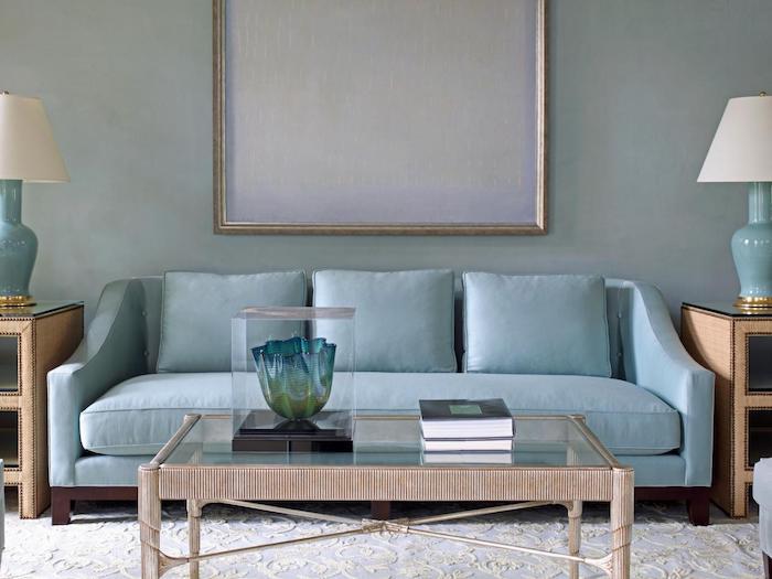 mur nuance gris tirant vers le bleu, canapé bleu, table basse en bois avec plateau en verre, tapis blanc, tables d appoint marron