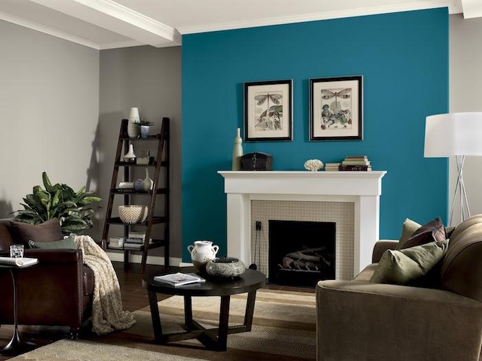 quelle couleur associer au gris perle, peinture gris et mur d accent bleu, cheminée blanche, parquet marron foncé, fauteuil en cuir et canapé gris, table basse en bois foncé
