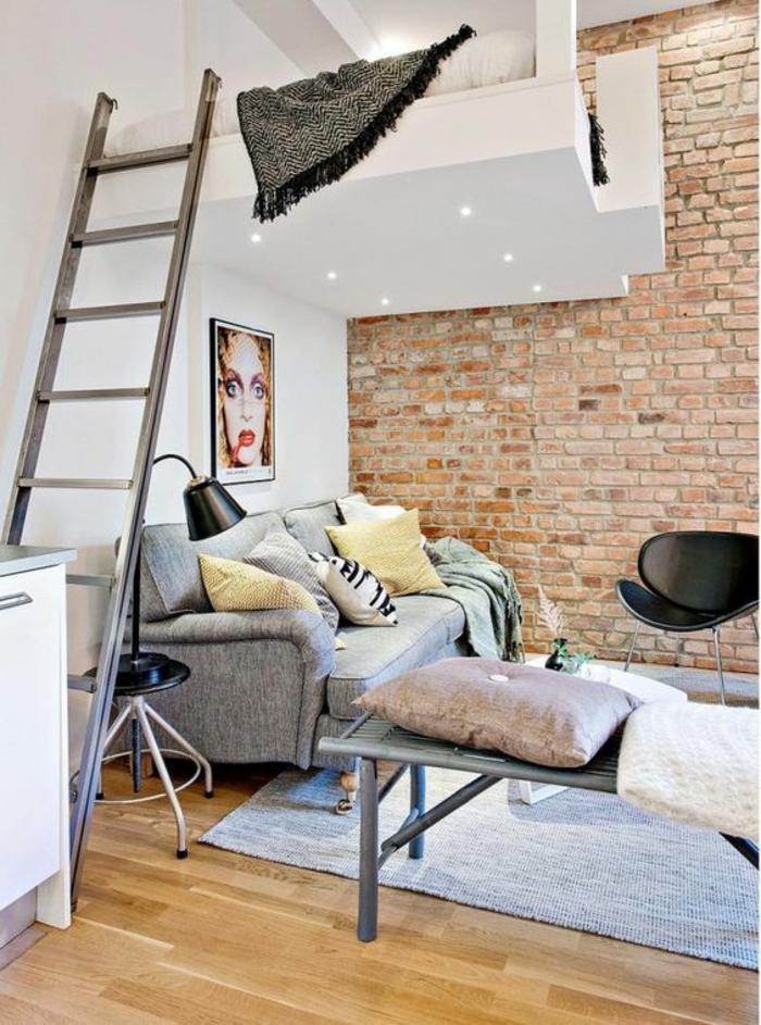 decoration interieure appartement avec un mur blanc et un mur en briques marron, parquet PVC en jaune, tapis carré en gris pastel, lit près du plafond, avec cube blanc, luminaire en métal noir