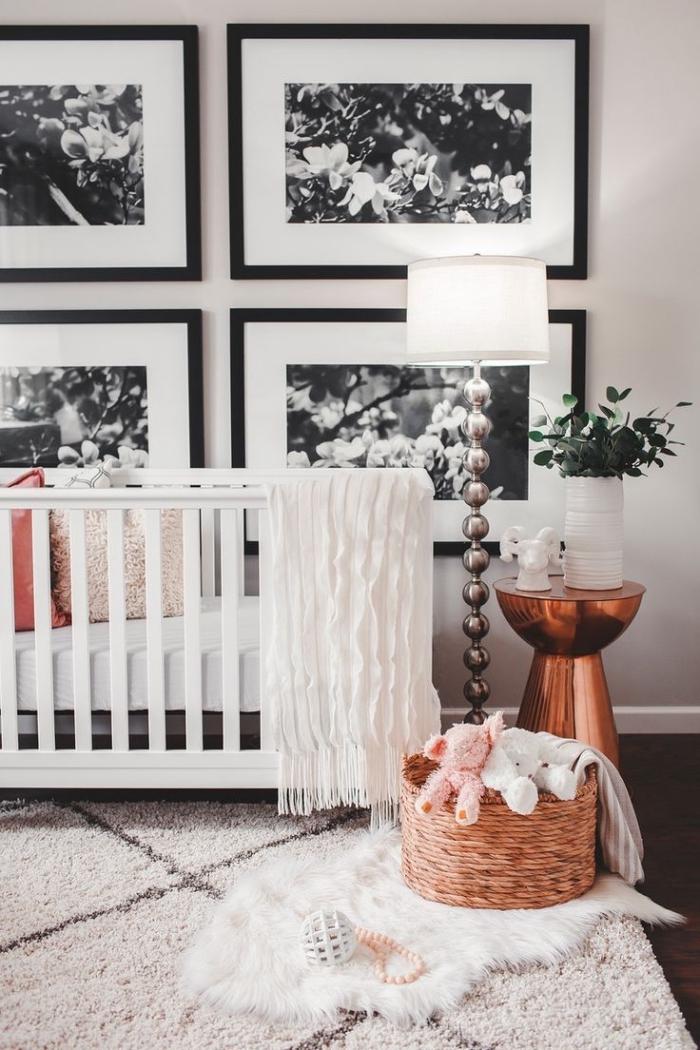 exemple d'une chambre bébé mixte aux murs blancs et plancher de bois foncé avec tapis moelleux et table de chevet cuivrée