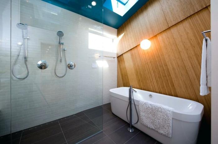 salle de bain sous pente, baignoire mise au sol, grands carreaux travertin, petit puits de lumière