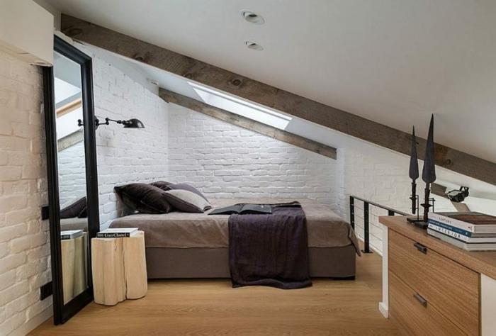 grand miroir, lit beige taupe, mur en briques, placard de bois, amenagement combles