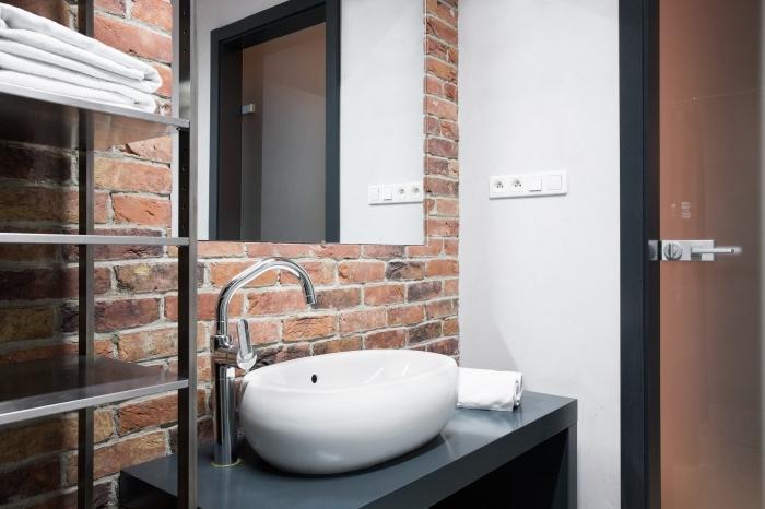 aménagement petit meuble salle de bain à espace limité aux murs en briques rouges avec meubles à design métallique et noir mate