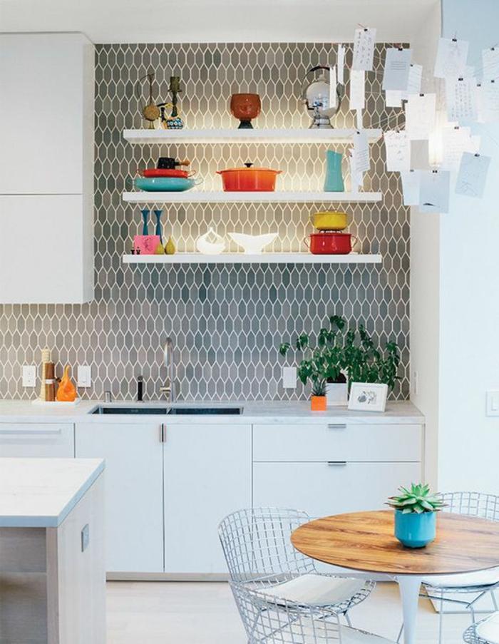 renover sa cuisine, mur et crédence en faïence bleue et grise, aux motifs ruches, petite table ronde en bois PVC, deux chaises métalliques blanches, îlot de cuisine en blanc et beige