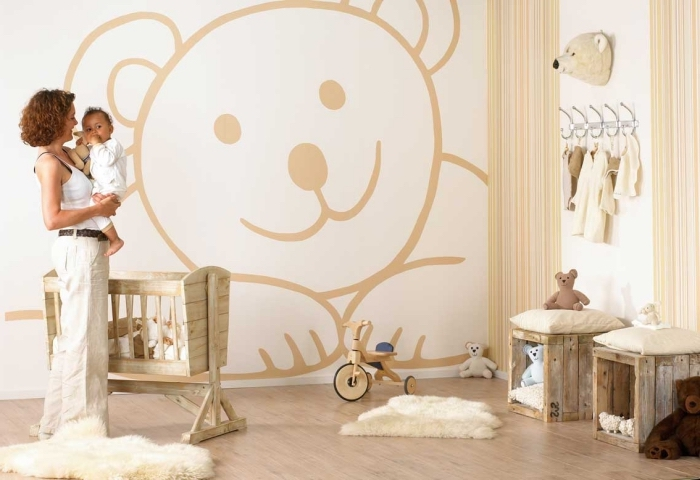 couleurs neutres blanc et beige dans la chambre bébé unisexe avec meubles de bois clair et tapis de faux fur blancs
