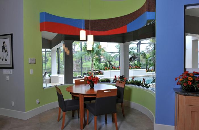 mur cinq couleurs, colonne en bleu royal, sol en carrelage ivoire, mur en couleur lavande, table ronde en bois cerise, quatre chaises en tissu noir et bois couleur cerisier