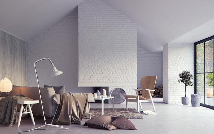 association de couleur avec le gris, canapé, tapis et coussins gris, sol gris effet béton, mur d accent en briques blanches, chaise bois, table basse blanche, design scandinave