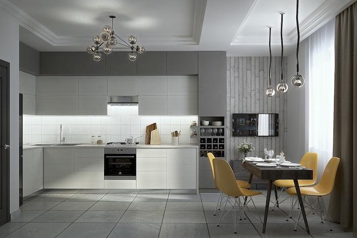 riddeaux, pan de mur et carrelage gris perle, cuisine blanche ouverte sur salle à manger décorée de table en bois et chaises jaunes