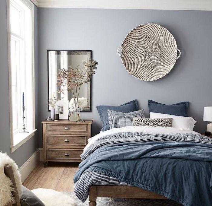 mur couleur peinture gris perle, linge de lit blanc, bleu et noir, lit et table de nuit bois foncé, parquet clair, panier en déco murale