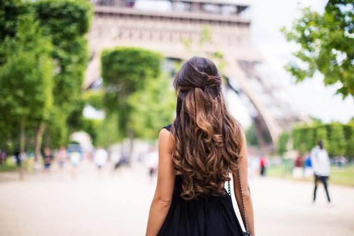 coiffure romantique aux cheveux bouclés et mi-attachés longs, modèle de robe noire courte, coloration cheveux châtain foncé aux pointes éclaircies dorés