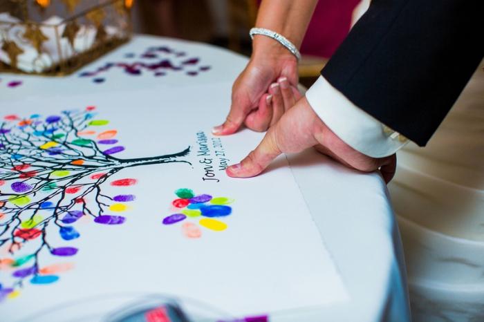 couple de jeunes mariés laissant leurs empreintes sur une toile à dessin naturel avec la date du mariage et leurs prénoms