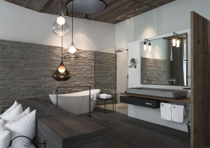 déco rustique et moderne dans une salle de bain au plancher de bois gris et mur en pierre et peinture blanche