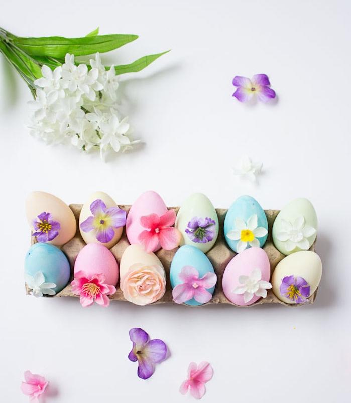 oeufs colorés de teintes différentes avec décoration de petites fleurs pour votre centre de table, activité manuelle paques