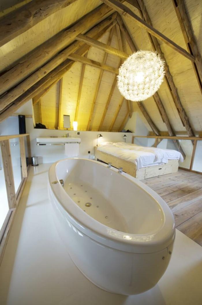 plafond poutres de bois, plafonnier rond féérique, grand bzignoire, chambre à coucher attique