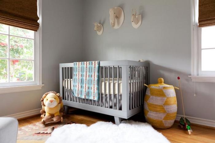 chambre complete bebe aux murs gris avec plancher de bois couvert de tapis moelleux blanc et jouets