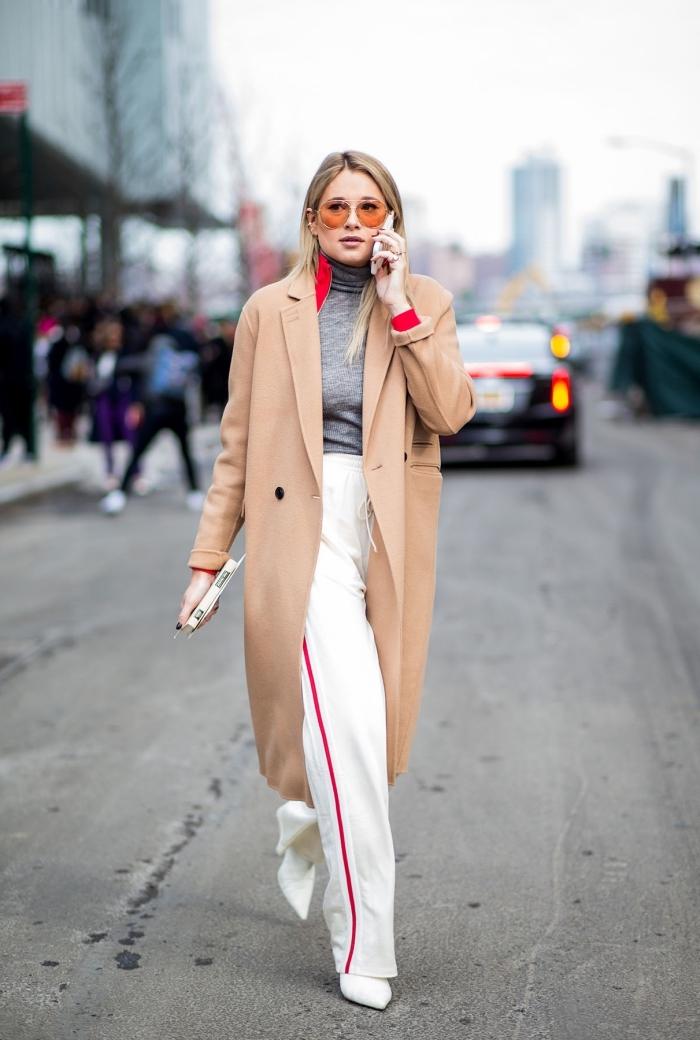 femme stylée avec pantalon fluide blanc et pull over gris, manteau long femme camel combiné avec lunettes de soleil orange