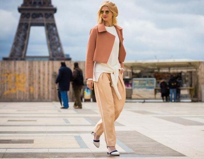 femme élégante avec pantalon fluide et capeline camel combinés avec chemise blanche et blazer marron pastel