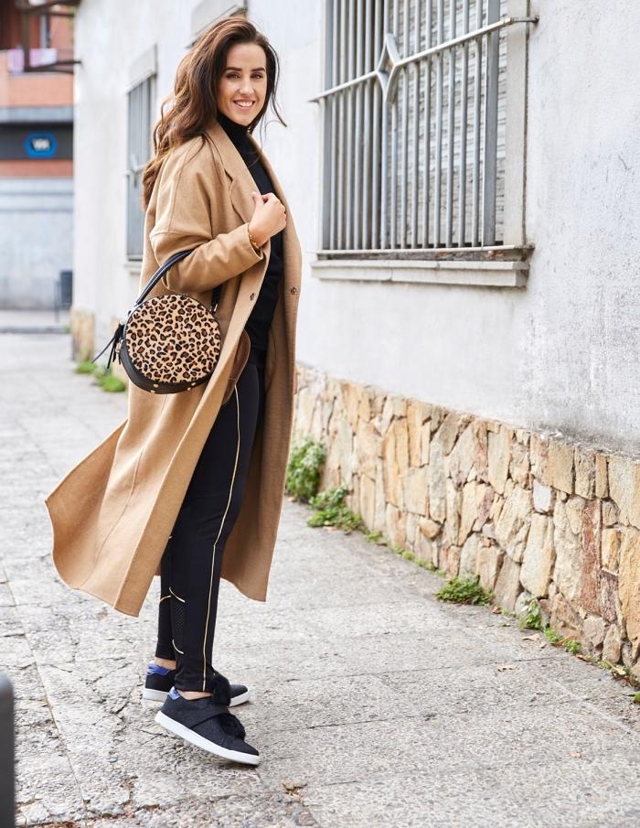 cheveux longs de couleur châtain cuivré légèrement bouclés, vision sportive en pantalon et baskets noirs avec manteau long beige