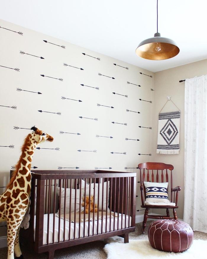 deco chambre bébé aux murs beige et plafond blanc avec meubles de couleur foncé et un grand girafe en péluche