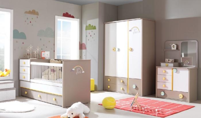 meubles blanc et beige dans la chambre bébé fille avec décoration à dessins nuages sur les murs et plusieurs jouets animaux