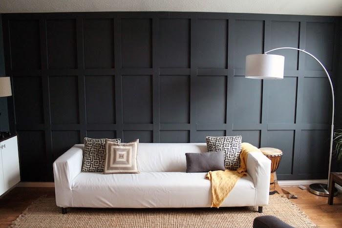 quelle couleur avec le gris, mur gris foncé, canapé blanc cassé, coussins décoratifs gris et beige, tapis beige, parquet clair