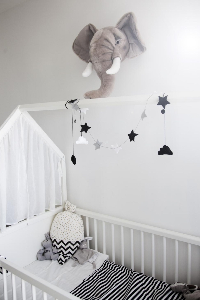 aménagement de la chambre bebe blanche avec lit à barreaux de bois blanc et décoration murale en forme de tête éléphant en péluche