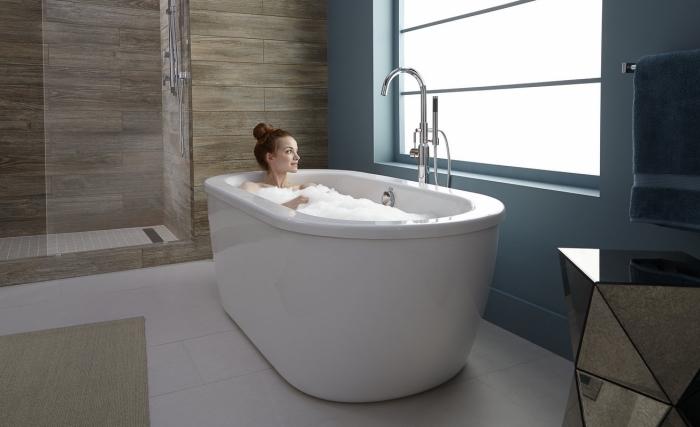 meuble de salle de bain aménagée en blanc et bois avec une peinture murale bleu pastel et grande fenêtre