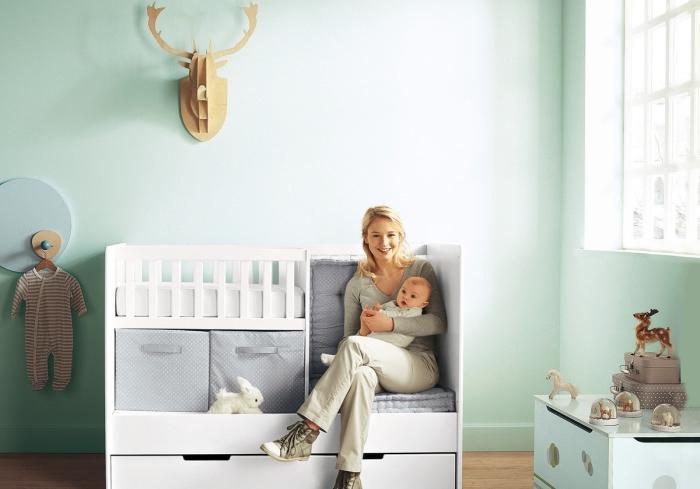 murs verts et plancher de bois clair dans la chambre bébé fille avec lit à barreaux et rangement de vêtements
