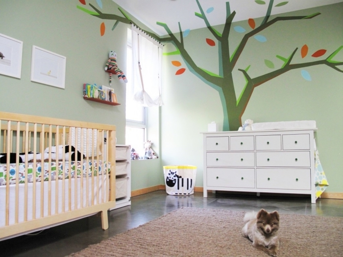 exemple de chambre bebe complete avec lit à barreaux de bois clair et armoire blanche sur plancher noir couvert de tapis beige