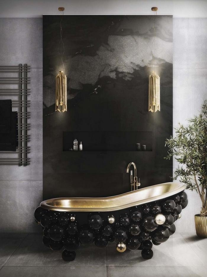 modele salle de bain luxueuse et élégante en couleurs foncées avec revêtement de pan de mur en noir marbre et appliques cuivrées