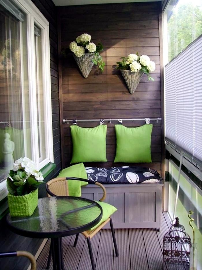 inspiration pour balcon bien décoré, malle canapé en bois, caisse fauteuil pour petit espace, barre murale porte coussins vert pomme