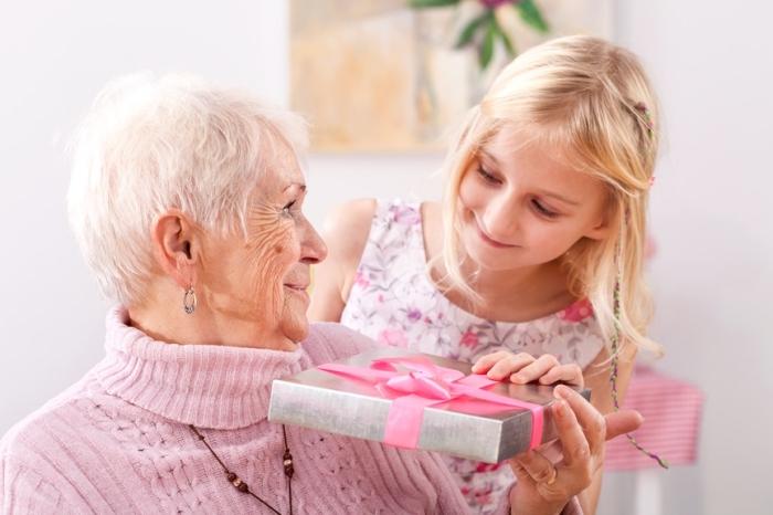 bricolage fete des grand mere, emballage joli au papier argenté et ruban rose, petite-fille aux cheveux blonds et sa grand-mère aux cheveux blancs
