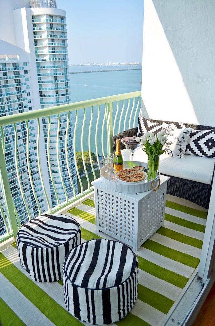 petit balcon en hauteur avec vue sur mer, mini terrasse appartement avec canapé et pouf noir et blanc