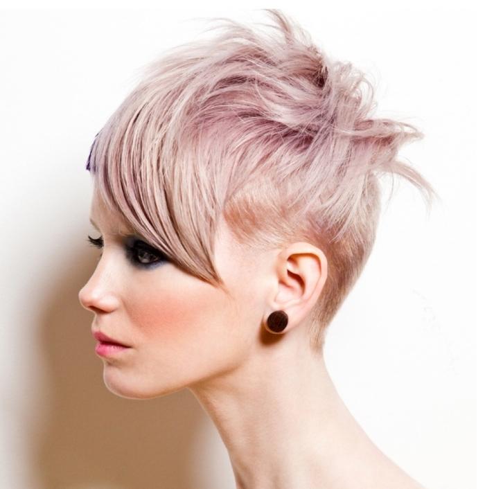 coloration moderne sur cheveux courts rasés sur le nuque et avec frange longue de côté, mèches rose pastel sur cheveux blonds