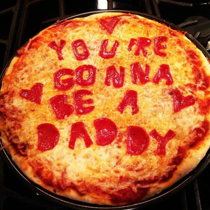 préparer un repas sollennel, pizza avec un texte tu seras un père écrit avec une sauce rouge