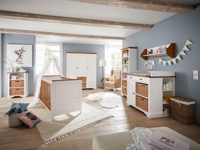 chambre bébé en style campagne avec murs peints en bleu clair et meubles blanc et bois, modèle de tapis beige avec frange sur un plancher de bois clair