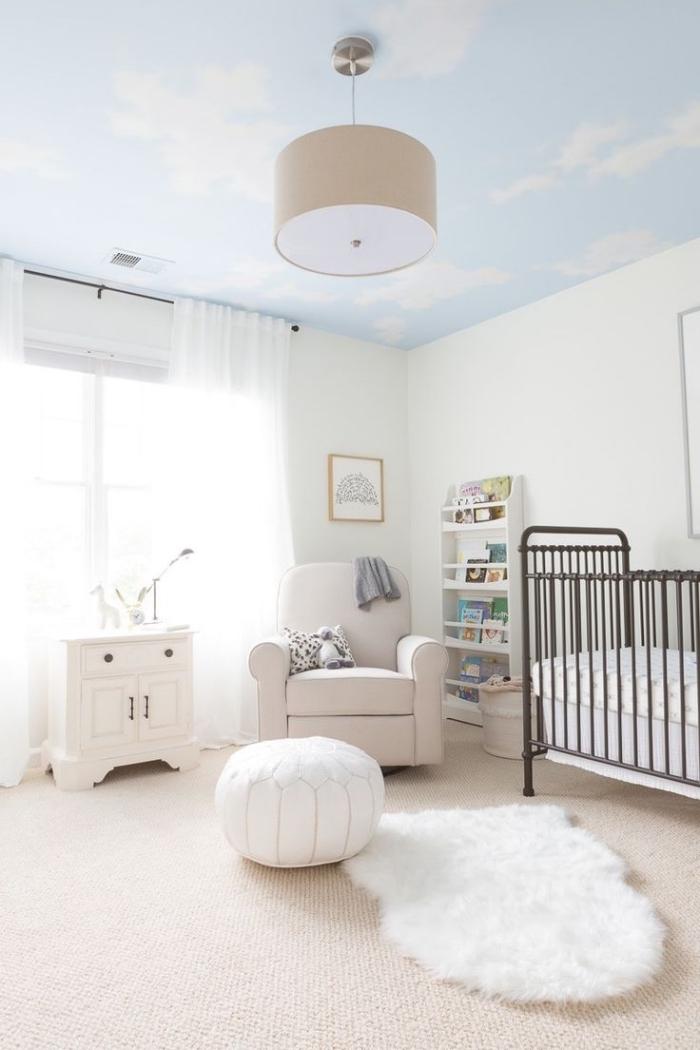 chambre bebe blanche au plafond à design ciel, accessoires cocooning sur tapis beige avec pouf et tapis blancs
