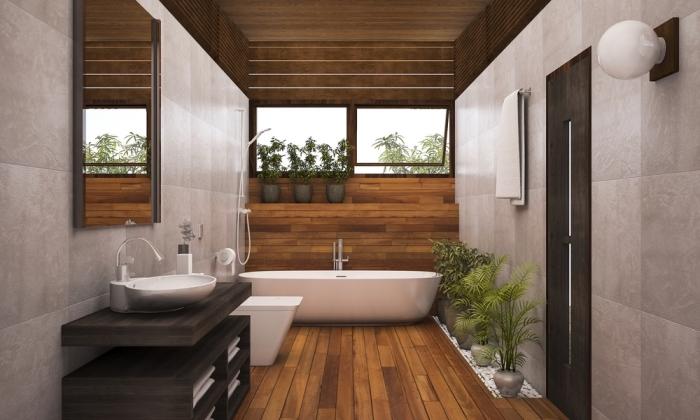 meuble salle de bain bois foncé, revêtement mural en carrelage beige avec pan en bois marron, plantes vertes pour ambiance relaxante