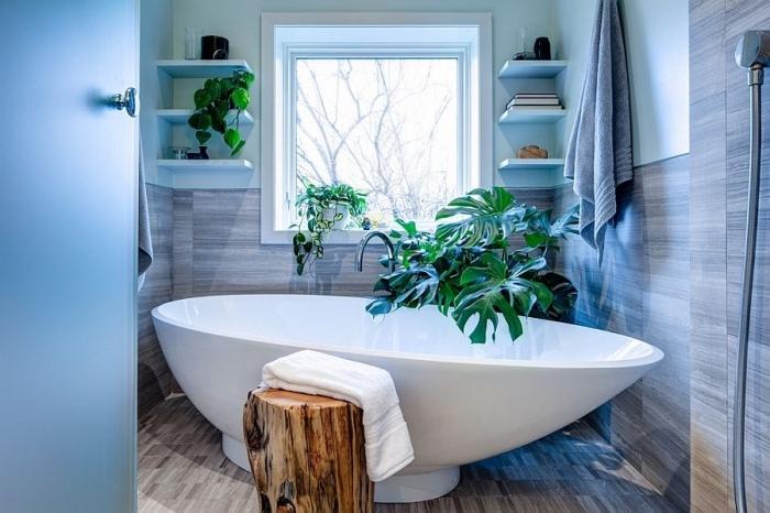 ambiance zen dans la salle de bain avec plantes vertes, rangement vertical de bois peint en blanc, modèle de baignoire autonome blanche
