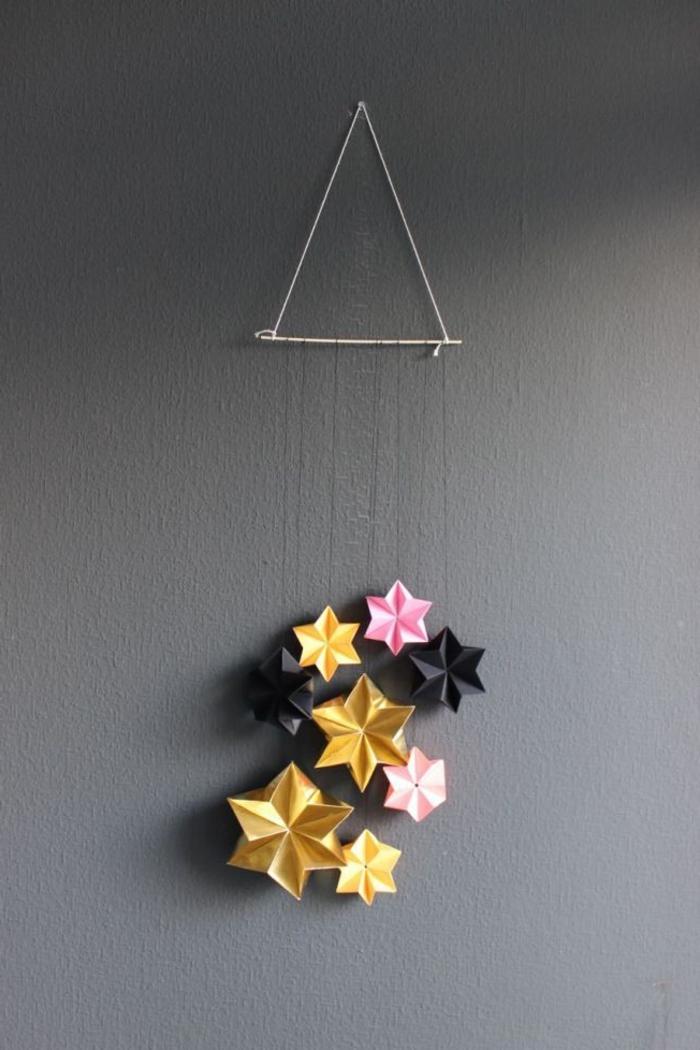 jolie suspension à la fois coquette et minimaliste avec des étoiles en origami de couleur et de taille différentes, idée pour un pliage papier original pour débutants