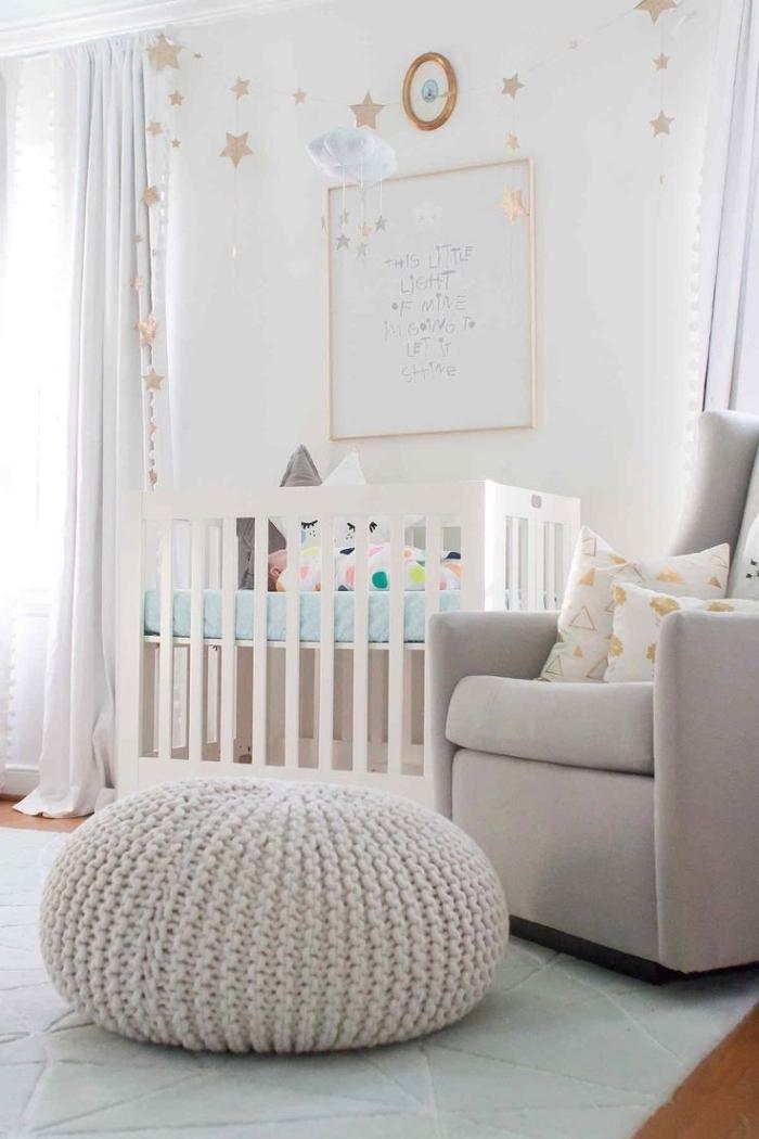 design intérieur dans la chambre bébé mixte aux murs blancs avec grande fenêtre et rideaux longs, modèle de pouf en crochet beige