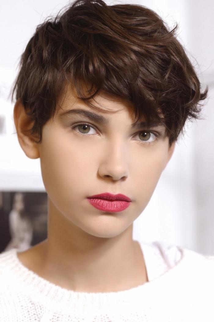 coloration naturelle châtain foncé sur cheveux courts et naturellement bouclés de style boyish, maquillage pour yeux verts aux lèvres rouge matte