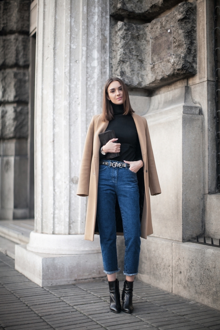 modèle de jeans haute taille femme avec ceinture combiné avec bottines de cuir noir et pull over noir, coupe de cheveux mi-longs de couleur châtain foncé