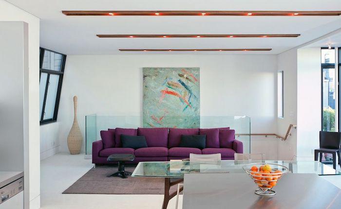 exemple quelle couleur associer au mauve, idée de canapé mauve décoré de coussins noirs, tapis gris, table en bois et verre et tableau abstrait au mur, éclairage au plafond appliques