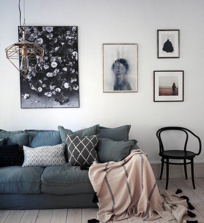 canapé nuance gris souris, coussins gris, couverture rose, parquet clair et deco murale de cadres art contemporaine, suspension geometrique originale