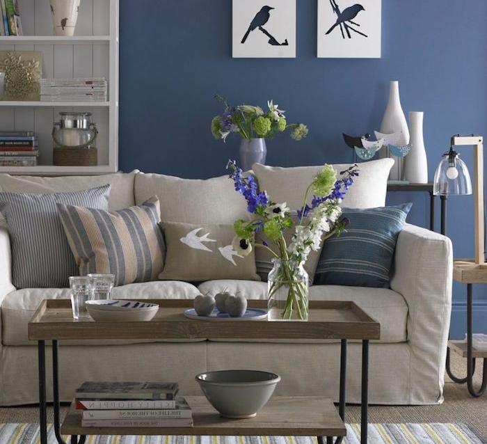idée quelle couleur avec le gris, canapé gris clair, coussins beige, gris et bleu, table basse en bois et metal mur décoré de peinture bleu nuit