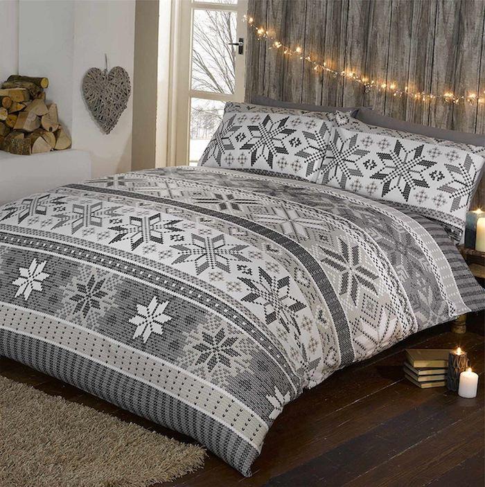 deco chambre rustique avec tete de lit en bois et petite lumières, parquet marron foncé, linge de lit gris et blanc à motifs flacon de neige