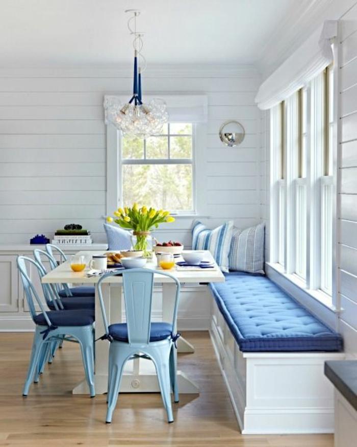 repeindre sa cuisine, pièce en bleu royal et blanc, style de maison qui donne sur la mer, chaises en métal bleu pastel avec des coussins en bleu royal, canapé en bois peint en blanc avec grand coussin rectangulaire en bleu royal, parquet lisse en nuances marron et beige, luminaire en métal bleu royal et motifs fleurs en verre blanc transparent