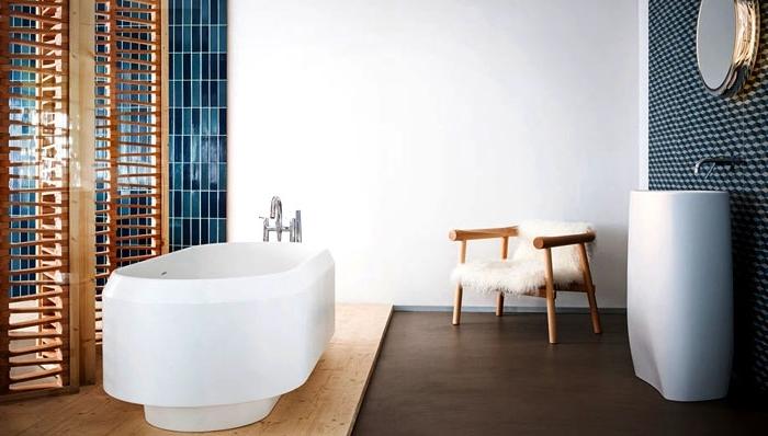 meuble salle de bain bois avec paroi séparant et chaise de bois couverte de housse en faux fur blanche, miroir oval à design métallique argenté