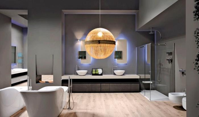 éclairage moderne pour la salle de bain aux murs gris et plancher de bois clair, meubles et équipement de salle de bain en blanc